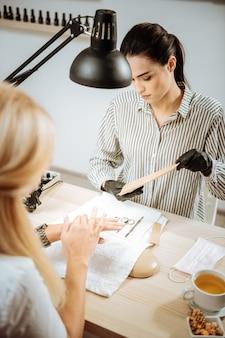 Mistrz zawodowy. widok z góry profesjonalnego doświadczonego mistrza manicure w pasiastej bluzce działającej