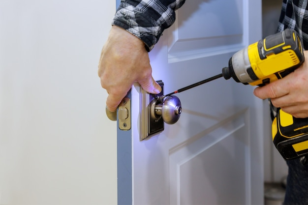 Mistrz ze śrubokrętem instaluje dostęp do drzwi pokoju nowy zamek w domu.