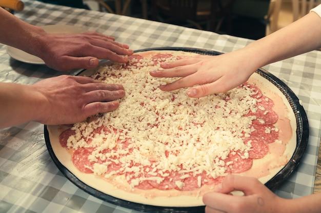 Mistrzowska klasa gotowania pizzy w pizzerii. przygotowanie pizzy do pieczenia w piekarniku.