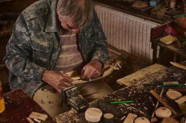 Mistrzowska klasa robienia drewnianych zabawek. ręce mistrza rzeźbienia w drewnie z dłutem i drewnianym przedmiotem.