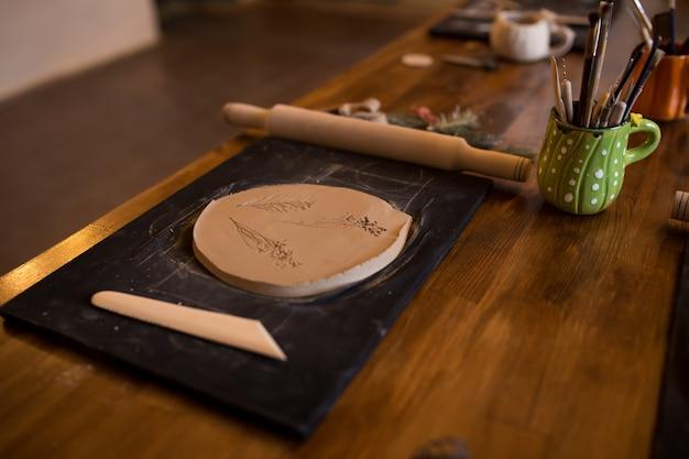 Mistrzowska klasa w modelowaniu glinianego dzbanka. stolik z gliną i narzędziem do kreatywności.