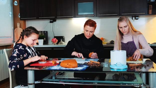Mistrzowskie ciasteczka przyrządzane w radosnej atmosferze w domu dwie kobiety i dziewczyna napełniające naczynie do pieczenia z...