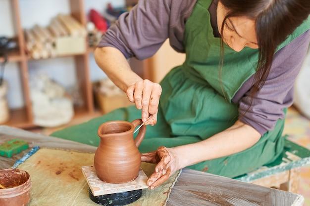 Mistrzyni garncarstwa rzeźbi w warsztacie dzban z czerwonej gliny.