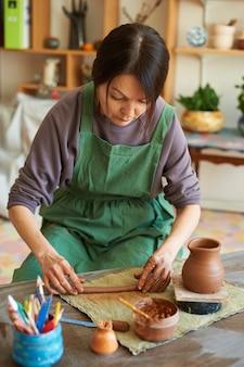 Mistrzyni garncarstwa w zielonym fartuchu rzeźbi dzban z czerwonej gliny.