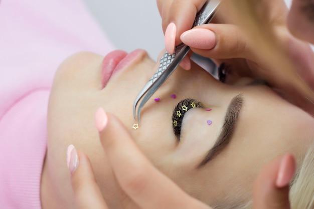 Mistrzyni przedłużania rzęs zdobi rzęsy dziewczynki cyrkoniami, serduszkami i gwiazdkami. kreatywne przedłużanie rzęs, makijaż oczu.