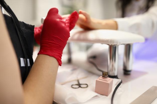Mistrzyni w gabinecie kosmetycznym pokrywa paznokcie klientów lakierem hybrydowym w miejscu pracy u fryzjera