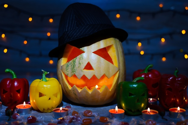 Mistyczne wakacje. cukierek albo psikus. halloweenowa dynia w kapeluszu. świece, płomień, cukierki, słodycze, efekt bokeh, zakrzywione twarze