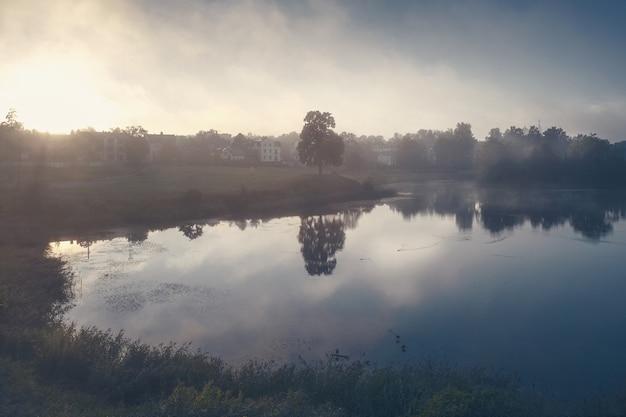 Mistyczny jesienny krajobraz z mgłą nad jeziorem w godzinach porannych