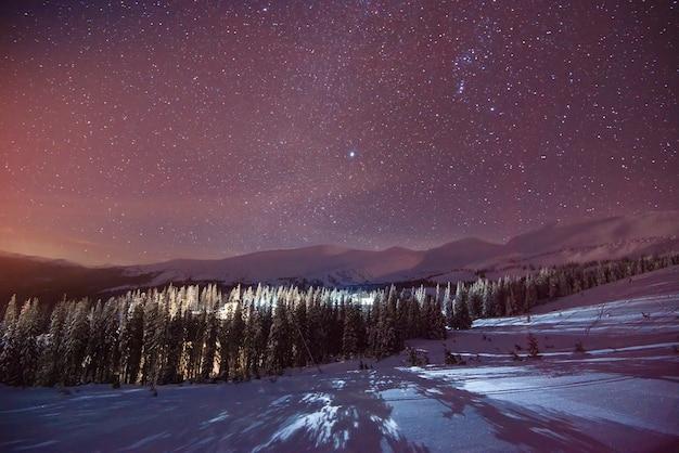 Mistyczny widok na zaśnieżone wzgórza w górskiej dolinie zimą na tle zachodzącego złotego słońca z mglistym niebem