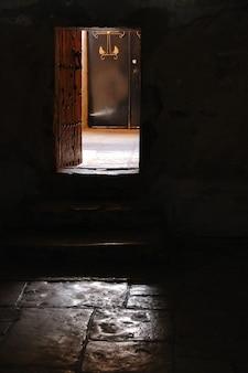 Mistyczny widok otwartych drzwi ze światłem słonecznym.