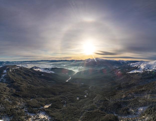 Mistyczny widok z lotu ptaka na stoki narciarskie, górskie wzgórza i drzewa pokryte śniegiem w słoneczny, pogodny dzień z błękitnym niebem. ekologiczna koncepcja turystyki. copyspace