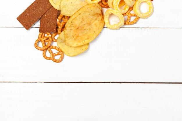 Mix przekąsek: precle, krakersy, frytki i nachos na stole