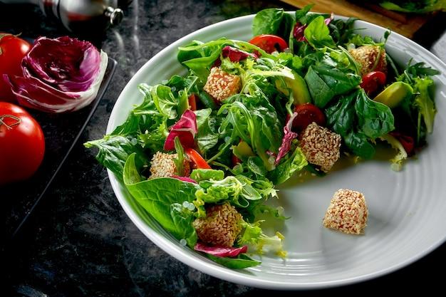 Mix sałat z łososiem, pomidorkami koktajlowymi i awokado, podawany na białym talerzu na stole z ciemnego marmuru. jedzenie w restauracji.