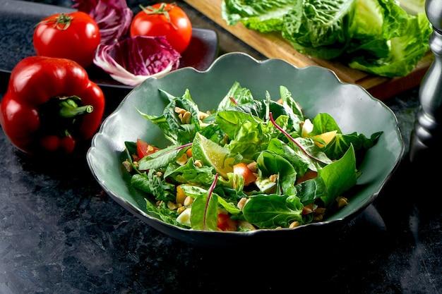 Mix sałat z persymoną, mozzarellą, szpinakiem i orzechami, podawany w zielonej misce na stole z ciemnego marmuru. sałatka wegetariańska. jedzenie w restauracji