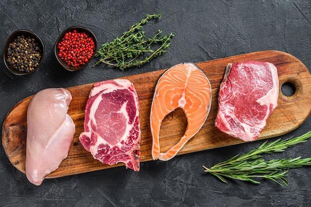 Mix surowych steków mięsnych z łososia, wołowiny, wieprzowiny i kurczaka. widok z góry.