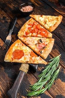 Mix włoskiej pizzy na drewnianej desce do krojenia.