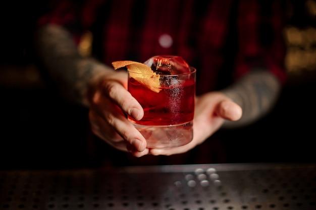 Mixologist trzyma szklankę mocnego świeżego koktajlu whisky