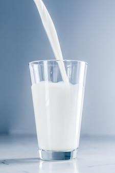 Mleczne zdrowe odżywianie i koncepcja śniadania światowy dzień mleka wlewający się do szkła na marmurowym stole