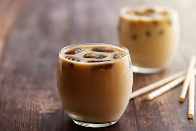 Mleczny koktajl kawowy w okularach z kostkami mrożonej kawy na drewnianym stole. widok z boku.