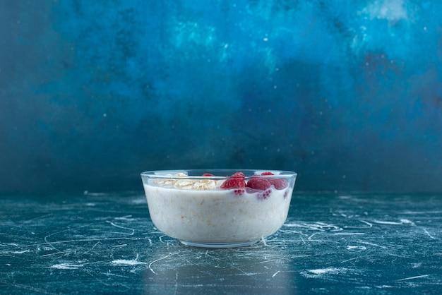 Mleczny koktajl z owocami i jagodami w szklanym kubku.
