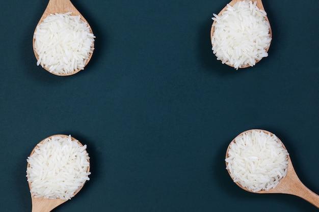 Mlejący ryż w drewnianej łyżce stawiają dalej zielonego deskowego tło