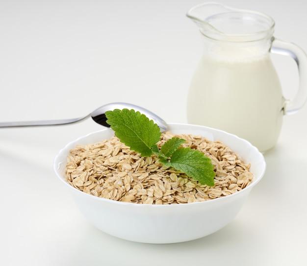Mleko-biała miska z suchymi płatkami owsianymi na białym tle, śniadanie