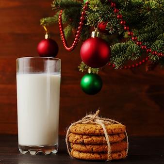 Mleko i ciastka dla świętego mikołaja pod choinką. , copyspace.