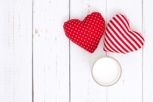 Mleko i czerwone serce na białym drewnianym stole