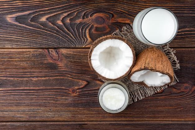 Mleko kokosowe i olej na ciemnym drewnie