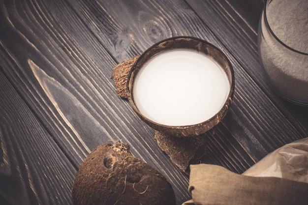 Mleko kokosowe na drewnianym tle. kokos i mleko kokosowe. świeże mleko kokosowe