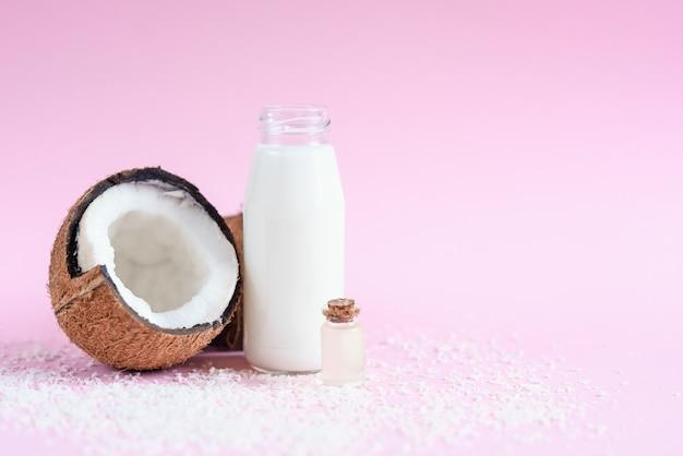 Mleko kokosowe w szklanej butelce, płatki kokosowe, olej i świeży kokos na różowym tle.