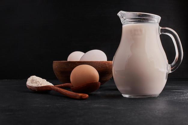 Mleko, mąka i jajka na czarnej przestrzeni.