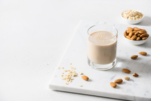 Mleko migdałowe i owsiane w szkle na białym tle z bliska