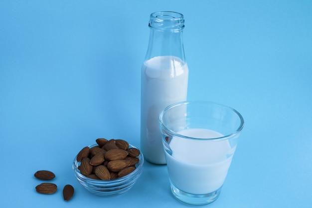 Mleko migdałowe w szklance i butelce na niebieskim tle