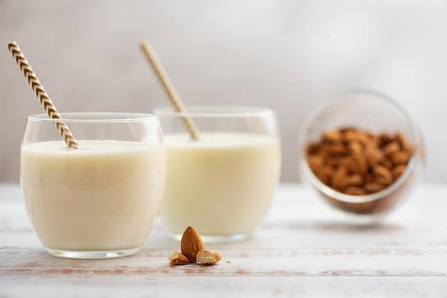 Mleko migdałowe w szklankach z migdałami na jasnym drewnianym stole.
