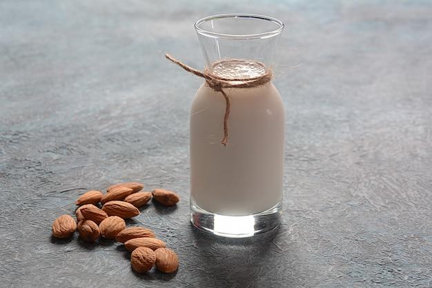 Mleko migdałowe w szklanych butelkach z migdałami na tle.