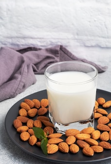 Mleko migdałowe w szklanych szklankach na ciemnym drewnianym stole.
