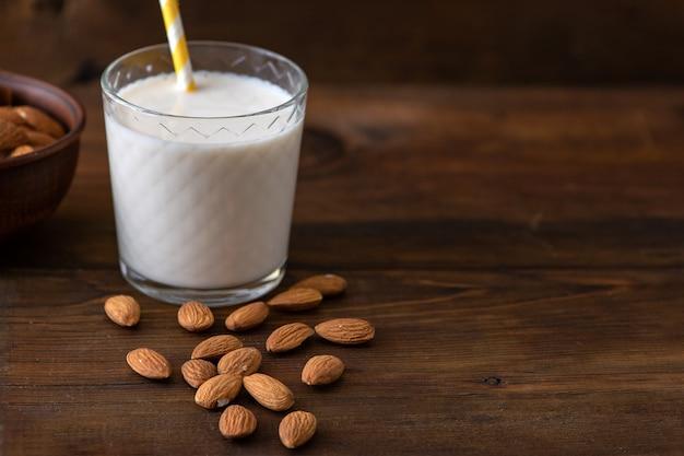 Mleko migdałowe z migdałami na ciemnym drewnianym stole.