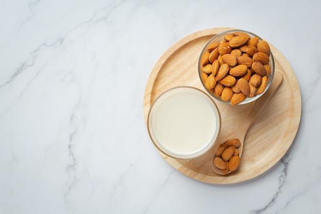 Mleko migdałowe z migdałami na marmurowym tle