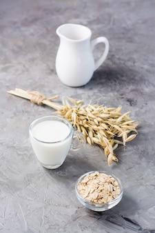 Mleko owsiane w filiżance, płatki owsiane i kłosy na stole. alternatywa dla mleka krowiego. zdrowe odżywianie. widok pionowy