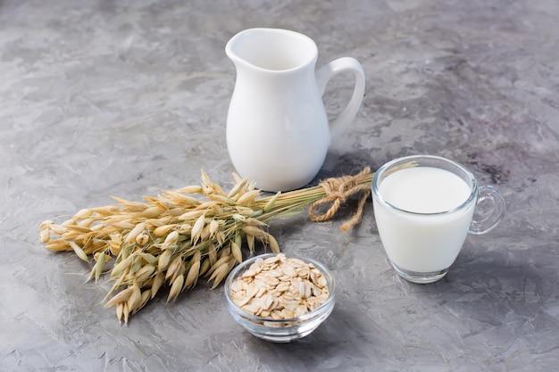 Mleko owsiane w filiżance, płatki owsiane i kłosy na stole. alternatywa dla mleka krowiego. zdrowe odżywianie
