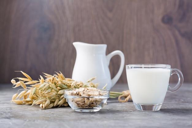 Mleko owsiane w filiżance, płatki owsiane i kłosy na stole. alternatywa dla mleka krowiego