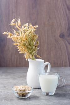 Mleko owsiane w filiżance, płatki owsiane i kłosy w dzbanku na stole. alternatywa dla mleka krowiego. zdrowa dietetyczna, niealergiczna żywność. widok pionowy