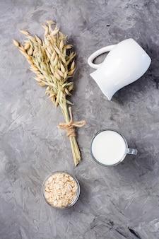 Mleko owsiane w filiżance, płatki owsiane i uszy na szarym tle. alternatywa dla mleka krowiego. zdrowe odżywianie. widok z góry i z pionu