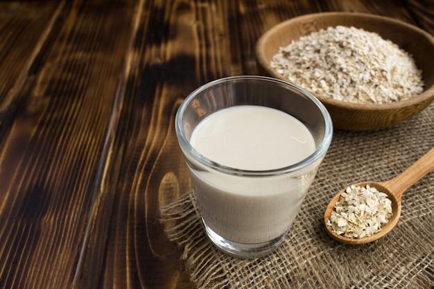 Mleko owsiane w szklance na drewnianym stole