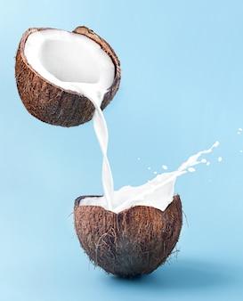 Mleko przelewa się z kokosa do kokosa z pluskiem.