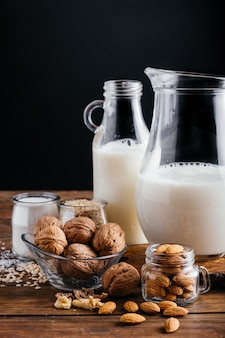 Mleko roślinne na tle drewna, mleko migdałowe, mleko orzechowe, mleko ryżowe i mleko kokosowe