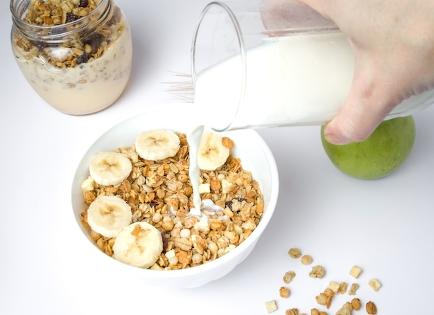 Mleko rozpryskiwania w misce świeżej muesli z mieszanką pszenicy, owsa i otrębów z suszonymi owocami i orzechami na białym tle.