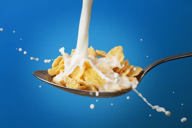 Mleko rozpryskuje się na łyżkę pełną płatków kukurydzianych, a kropelki rozlewają się po całym naczyniu