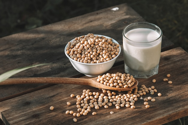 Mleko sojowe fajne i soi na drewnianym stole tło z oświetleniem w godzinach porannych